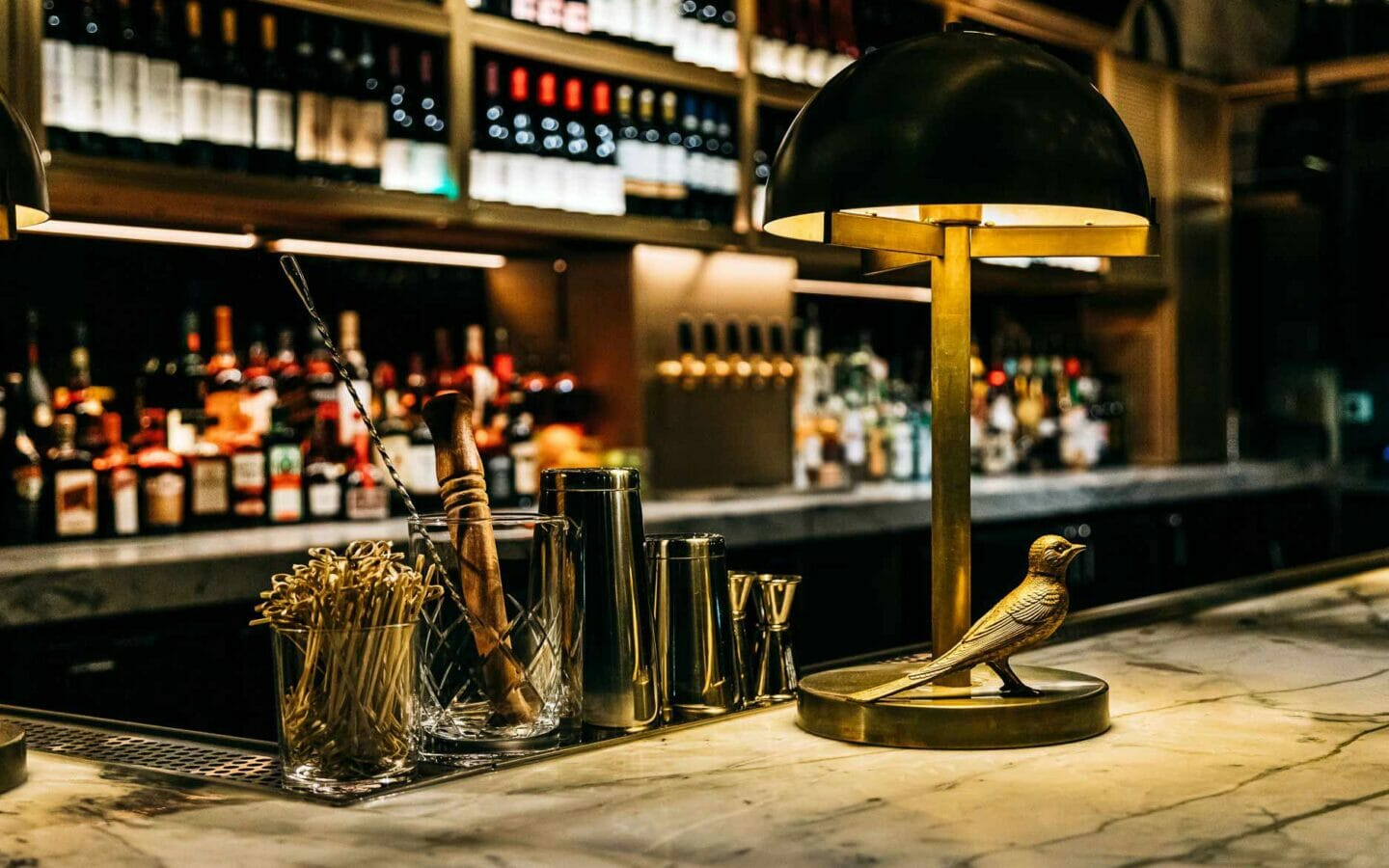 a dome-shaped lamp on a marble bar in a dimly lit luxurious lounge