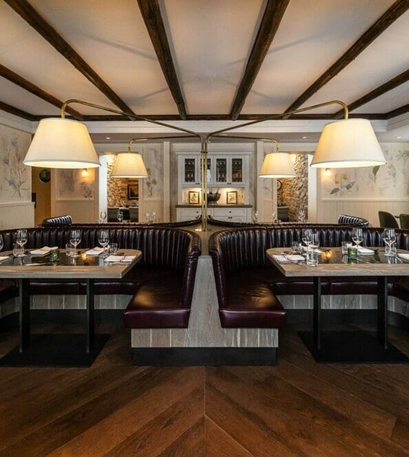two large horseshoe shaped tables set for service in a historic dining room