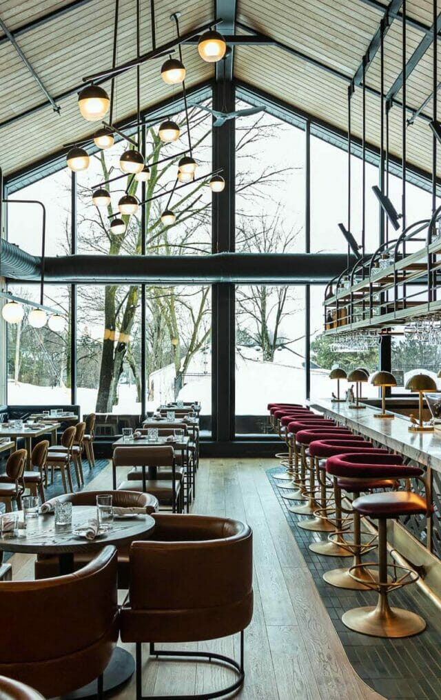 a glamorous lounge in a historic building floor to ceiling a-frame windows looking out on a snowy landscape