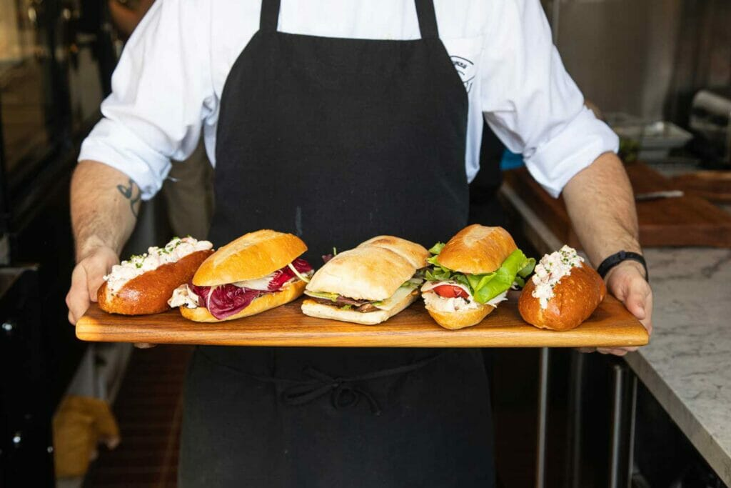 man holding up a wooden board with a selection of five sandwiches on it
