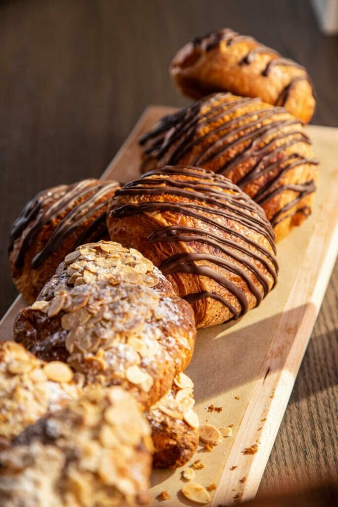 pastries with chocolate drizzle on a wooden board