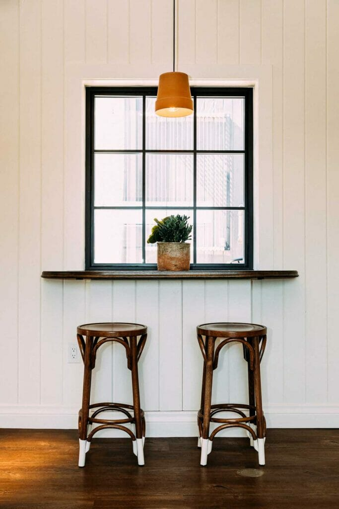 two bar stools under a window and mantel